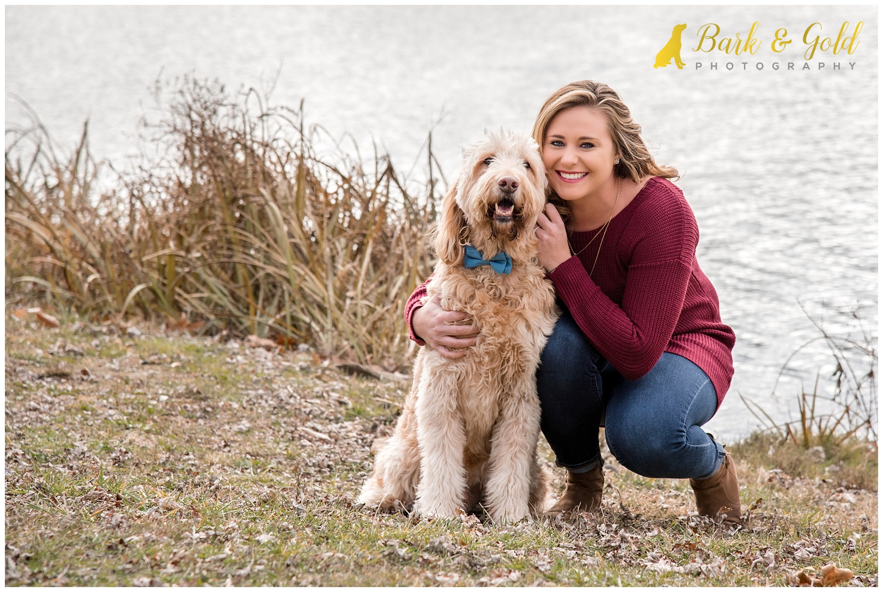 young woman cuddling a senior goldendoodle by the lake at North Park in Gibsonia