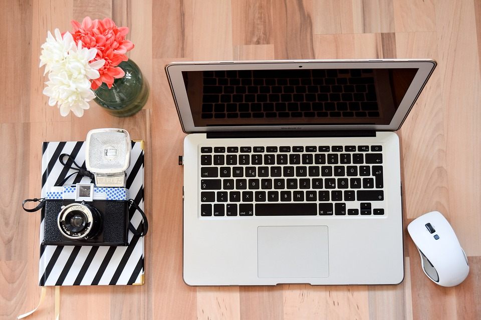 wooden desk with computer, camera, vase of flowers, and notebook