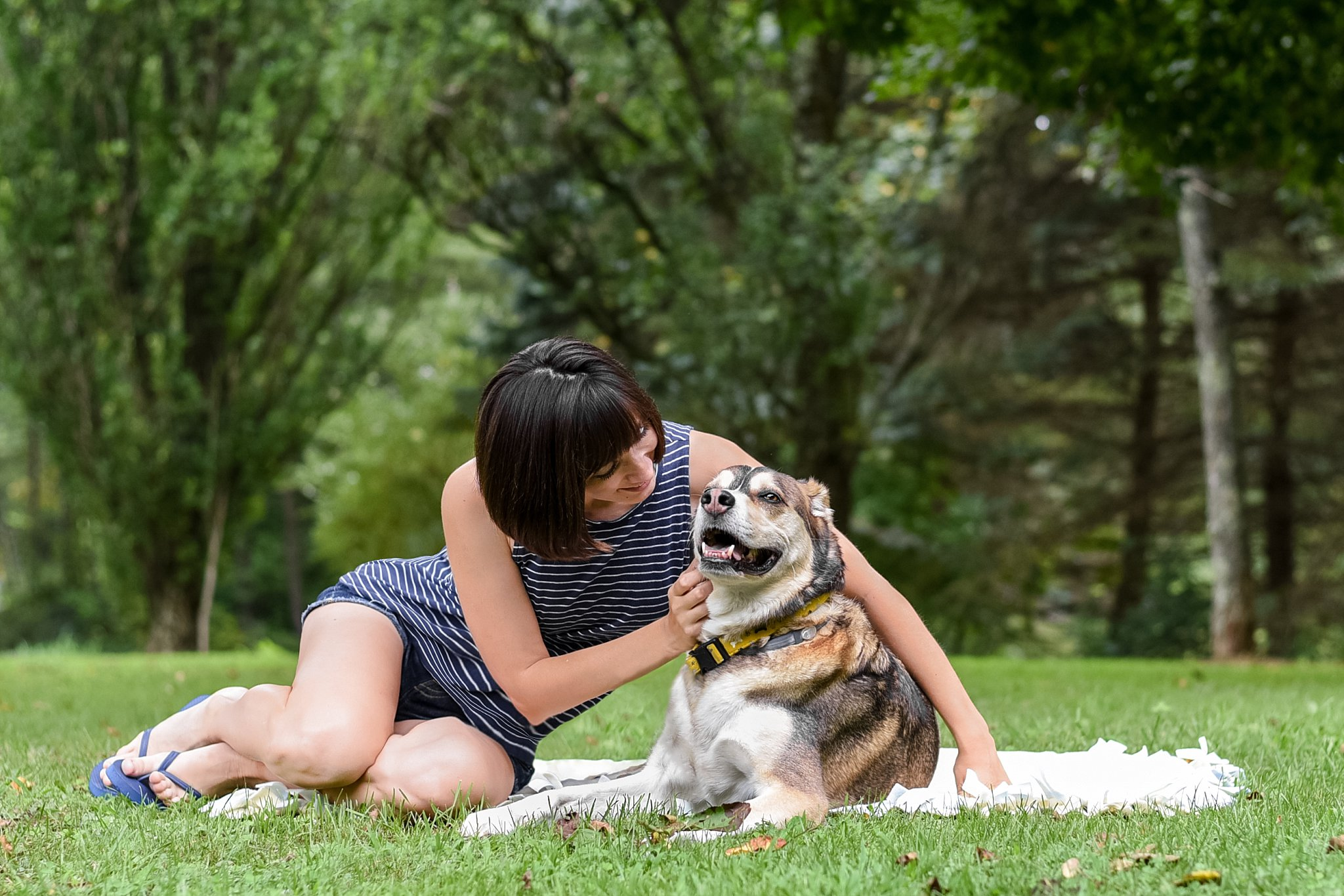 Photographer Jessica Wasik cuddling her dog Hunter on a blanket in a grassy area