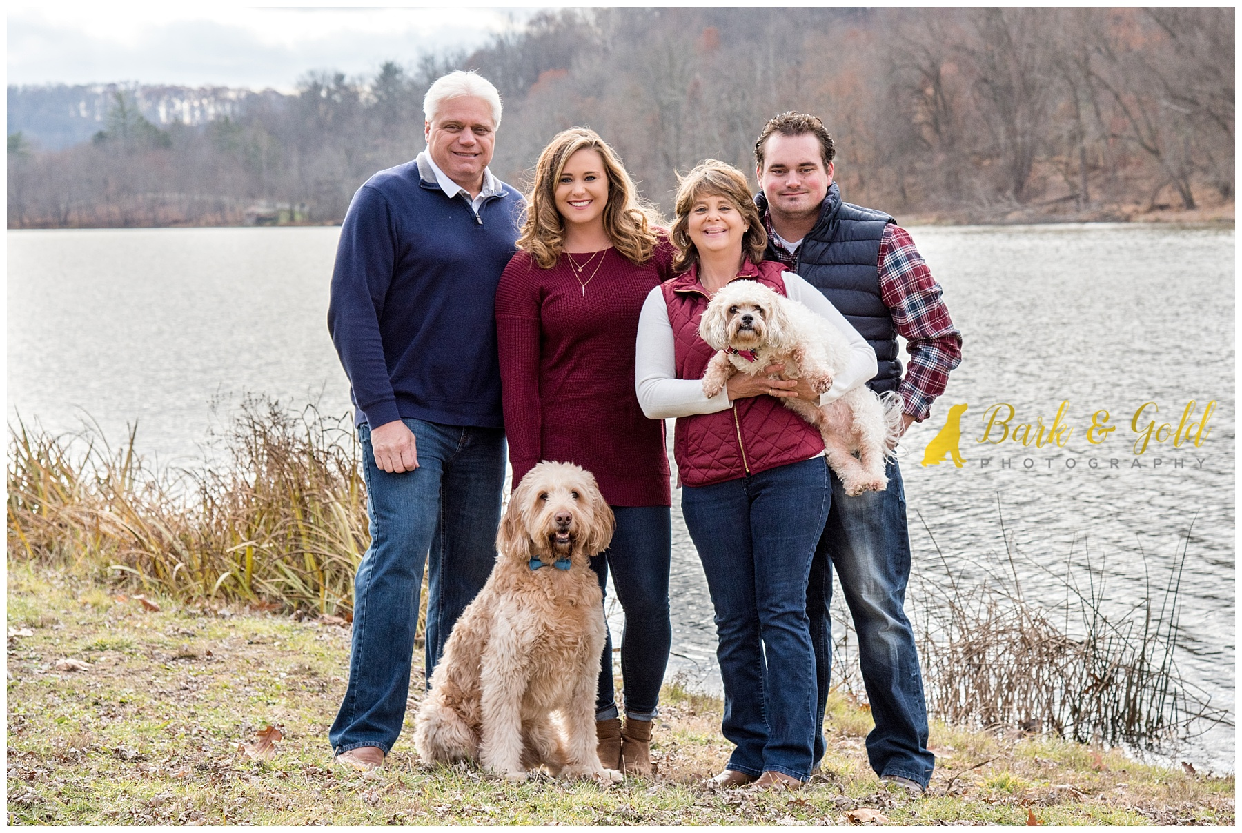 family poses with two dogs by lake and boathouse at North Park