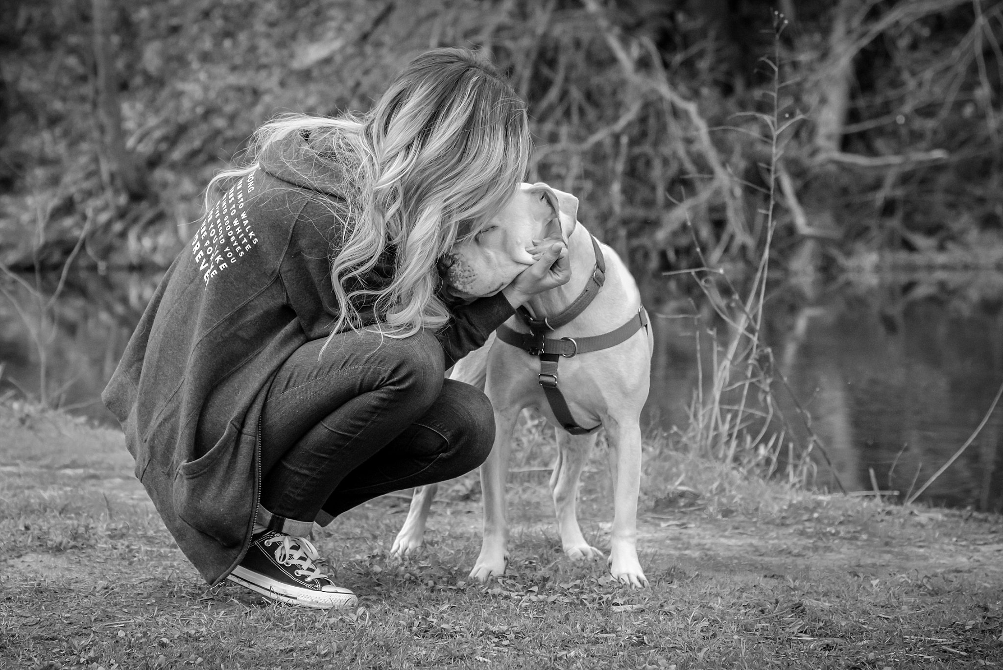 woman kissing pit bull on the head